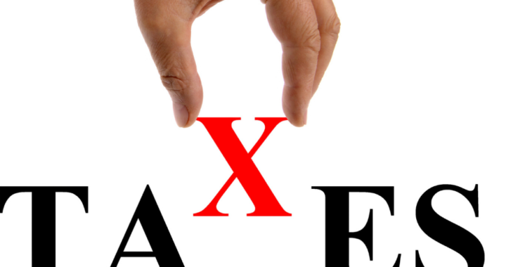 Hand putting the X in the word taxes.